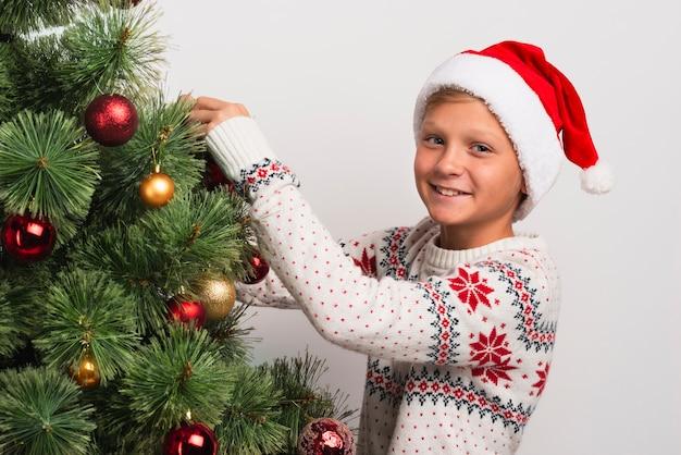 Niño feliz decorando el árbol de navidad
