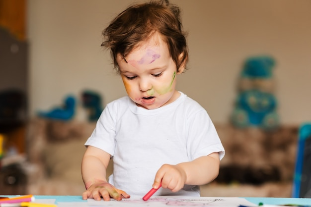 Niño feliz dibuja con lápices de colores en un álbum