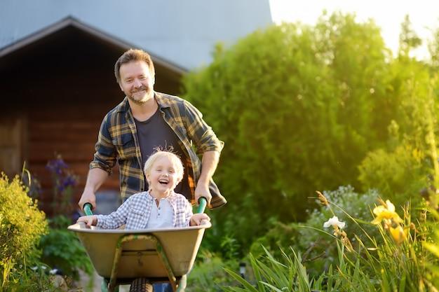 Niño feliz divirtiéndose en una carretilla de mano empujando por papá en el jardín doméstico en un cálido día soleado.