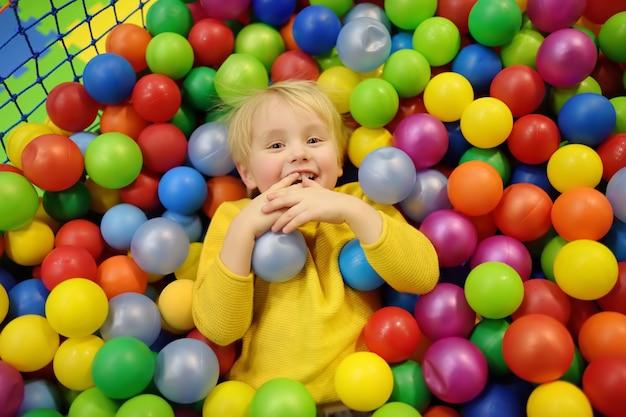Niño feliz divirtiéndose en el hoyo de la bola con bolas de colores