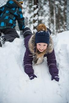 Niño feliz divirtiéndose jugando con nieve en día de invierno