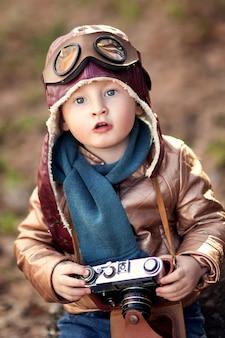 Niño feliz y elegante con la cámara en las manos en una chaqueta de cuero marrón con un hidromiel de juguete