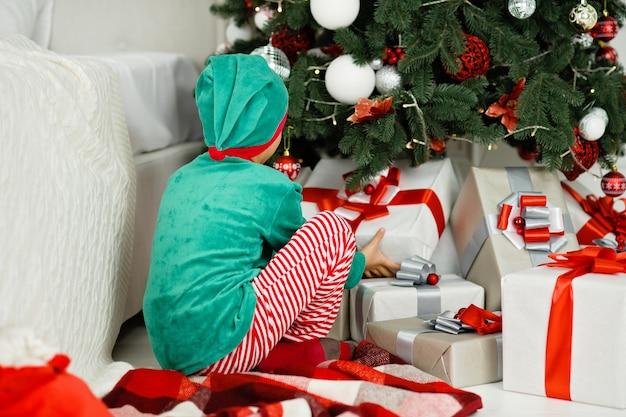 Niño feliz emocionado con caja de regalo de navidad.