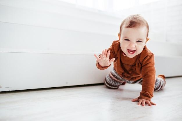 Niño feliz en suéter naranja juega con plumas en el piso
