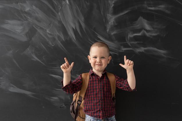 Niño feliz en la escuela se encuentra en la pizarra.