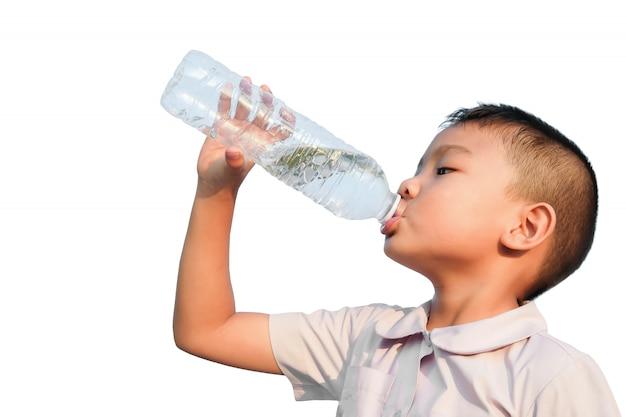 Niño feliz estudiante asiático niño bebiendo un poco de agua de una botella de plástico.