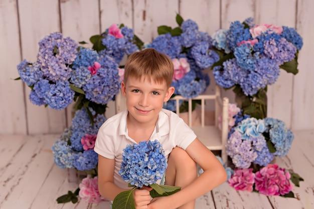 Niño feliz en el estudio sobre un fondo blanco con flores de hortensias rosas y azules