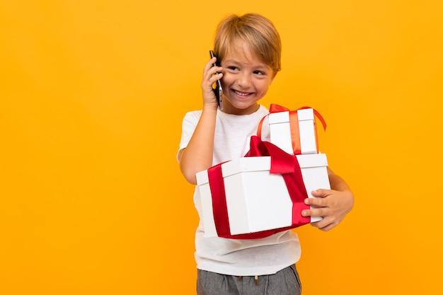 Niño feliz hablando por teléfono y sosteniendo una caja de regalo