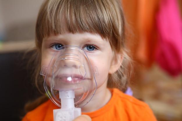 Niño feliz hace inhalación en casa para