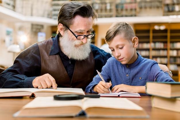 Niño feliz haciendo los deberes escolares con anciano, sentado a la mesa en la biblioteca de la ciudad vintage.