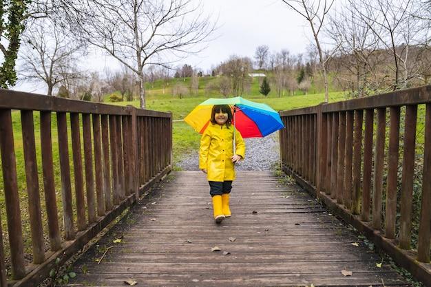 Niño feliz con un impermeable amarillo y botas de lluvia y un paraguas de colores del arco iris en la mano caminando por un puente en un bosque