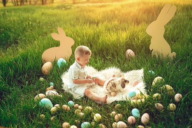 Niño feliz en juego con lindo conejito esponjoso