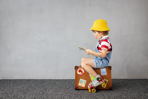 Niño feliz jugando al aire libre. niño sonriente soñando con viajes y vacaciones de verano. concepto de imaginación y libertad. texto en pegatinas: italia, roma; istanbul, turquía.