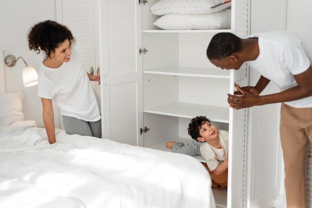 Niño feliz jugando al escondite con sus padres