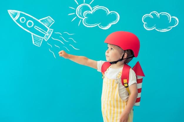 Niño feliz jugando con alas de papel de juguete contra la pared azul en casa.