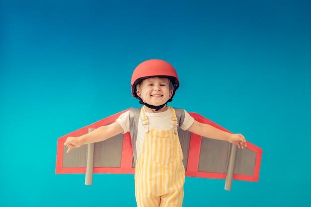 Niño feliz jugando con alas de papel de juguete contra la pared azul.