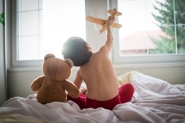 Niño feliz jugando con avión de juguete de madera y oso de peluche en el dormitorio