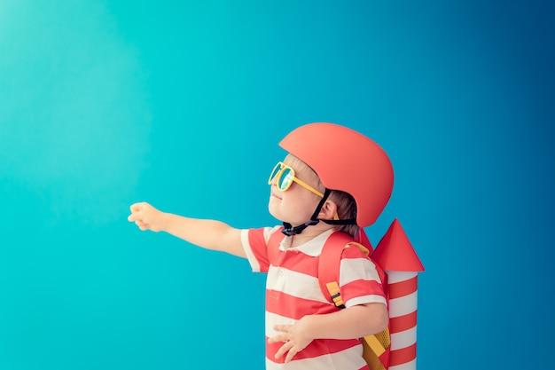 Niño feliz jugando con cohetes de papel de juguete contra la pared azul.