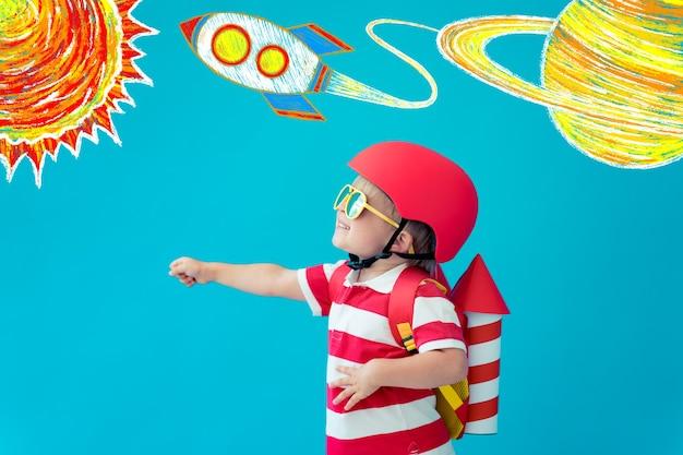 Niño feliz jugando con jet pack de papel de juguete contra la pared azul en casa.