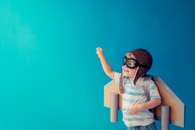 Niño feliz jugando con jetpack de papel de juguete contra la pared azul.