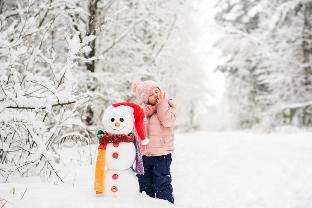 Niño feliz jugando con muñeco de nieve. niña divertida en un paseo en el invierno al aire libre