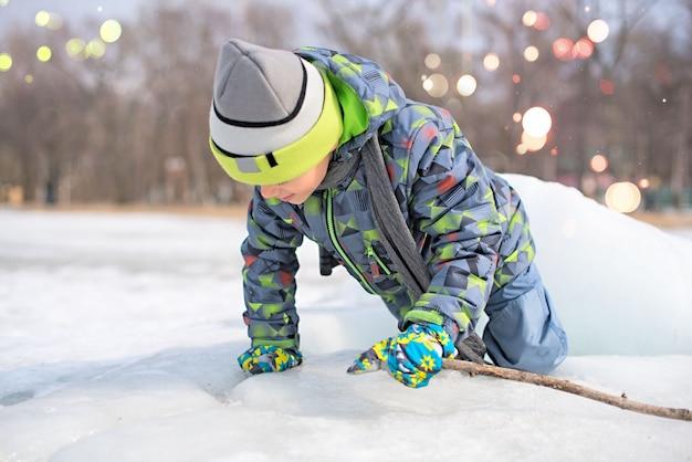 Niño feliz jugando en la nieve