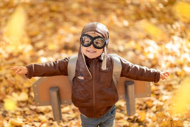 Niño feliz jugando en otoño