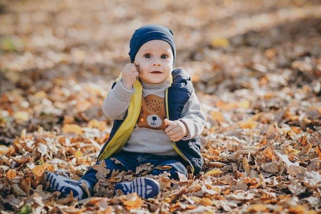 Niño feliz jugando en una pila de hojas durante el otoño. lindo bebé en otoño parque con hojas amarillas