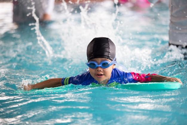 Niño feliz jugando en la piscina.