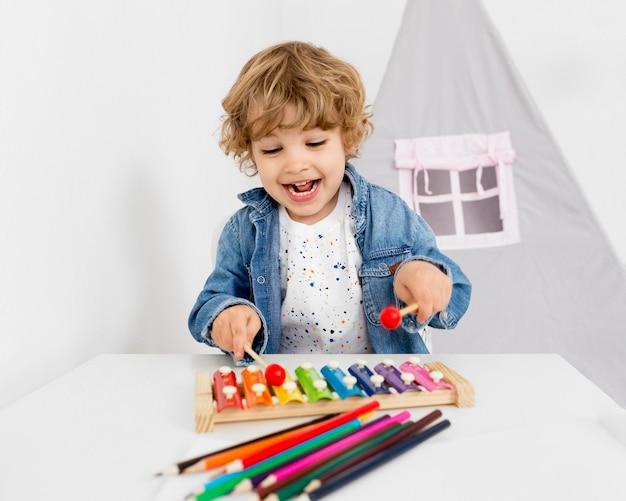 Niño feliz jugando con xilófono