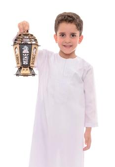 Niño feliz con linterna sobre fondo blanco.