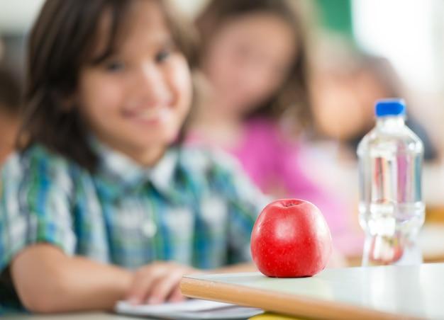 Niño feliz con manzana y botella de agua sentado en classrom y sonriendo