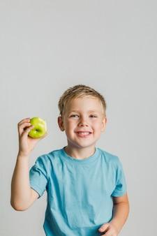 Niño feliz con una manzana verde