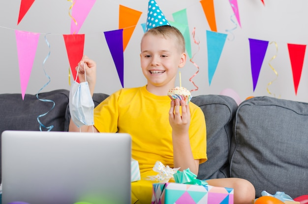 Niño feliz en medicina mascarilla celebra cumpleaños por video llamada a la computadora portátil