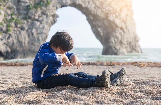 Niño feliz mirando hacia abajo jugando con piedras en sus piernas junto al mar con fondo borroso