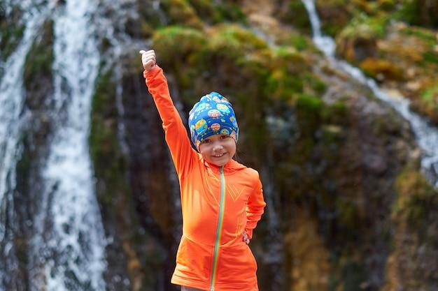 Niño feliz mujer viaje con mochilas pulgar arriba. primer plano de retrato de deportes al aire libre