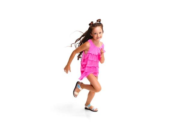 Niño feliz, niña caucásica pequeña y emocional saltando y corriendo aislado en blanco
