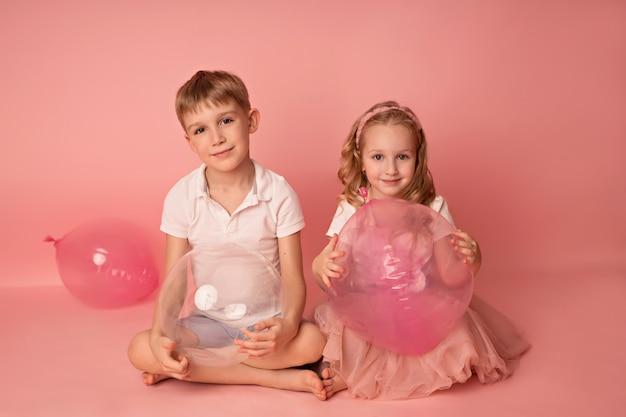 Niño feliz niña y niño sobre un fondo rosa con globos. celebracion. cumpleaños