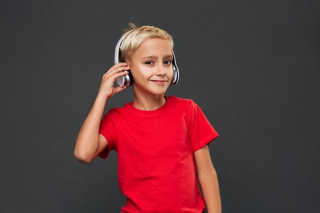 Niño feliz niño escuchando música con auriculares.