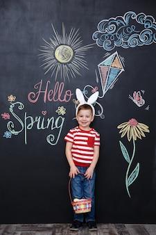 Niño feliz con orejas de conejo y sosteniendo la canasta de pascua