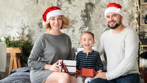 Niño feliz y padres juntos el día de navidad
