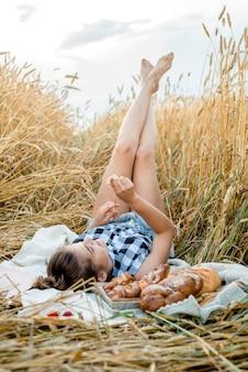 Niño feliz con pan en campo de trigo de otoño amarillo. un campo con mazorcas maduras. una niña sentada sobre una colcha, frutas y bayas frescas, pan y panecillos en una canasta. picnic en el pueblo al aire libre.