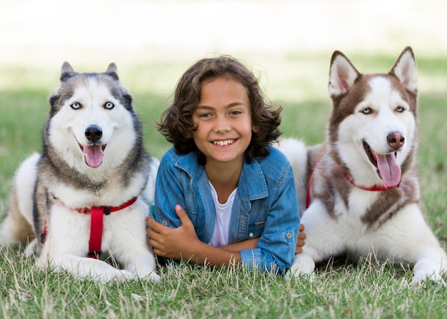 Niño feliz posando con sus perros en el parque