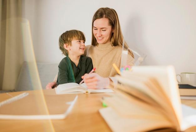 Niño feliz que enseña el maestro en casa