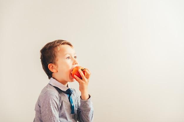 Niño feliz que muerde una manzana para cuidar sus dientes, aislando en el fondo blanco.