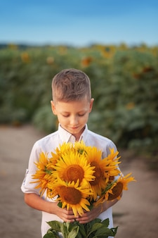Niño feliz con el ramo de girasoles hermosos en campo del girasol del verano en puesta del sol. día de la madre