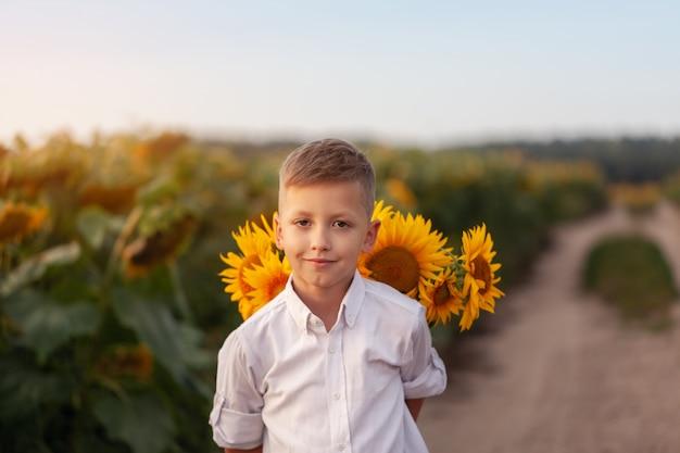 Niño feliz con el ramo de girasoles hermosos en campo del girasol del verano en puesta del sol.