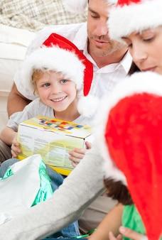 Niño feliz con un regalo de navidad sentado en el piso