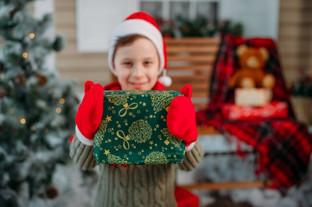 Niño feliz con regalos en decoraciones de navidad