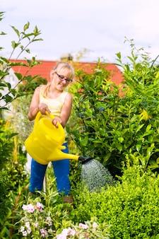 Niño feliz regando las flores en el jardín